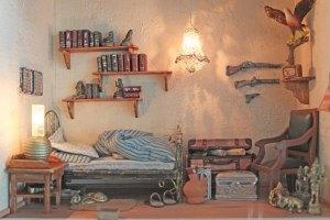 Øverste etage er indrettet til soveværelse med jernseng, lænestol, rejsekuffert, kort, bøger, rifler og mange andre ting. Lampen er lavet af ståltråd og små klare perler