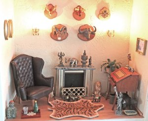 Underste etage er pejsestuen med skrivepult, lænestol og mange af de fine bronze figurer. Dyrehovederne er fra en pakke med vilde dyr (plastik) købt i Skandinavisk Dyrepark.