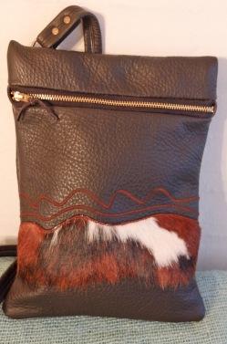 Denne taske er af sort skind med pynt af en strimmel broget ko skind og lidt pyntesyninger. Størrelse 20 x 30 cm