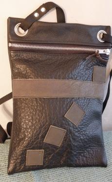 Denne taske er af sort skind med olivengrønne pynte firkanter og mavebælte. Størrelsen er 20 x 28 cm
